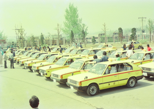 Deluxe taxi standing by at district office for filial tour to Haengjusanseong Fortress (1991)